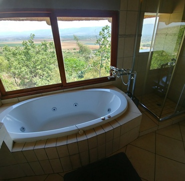 Red Sky Lodge - Upper west spa bath and shower with a view over the Hartbeespoort valley